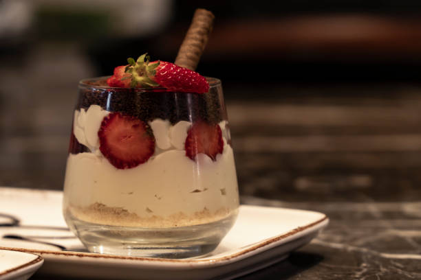 Layered dessert or Magnolia with cocoa biscuit and pudding in the glass cup. There are strawberry and raspberry on the desserts. stock photo