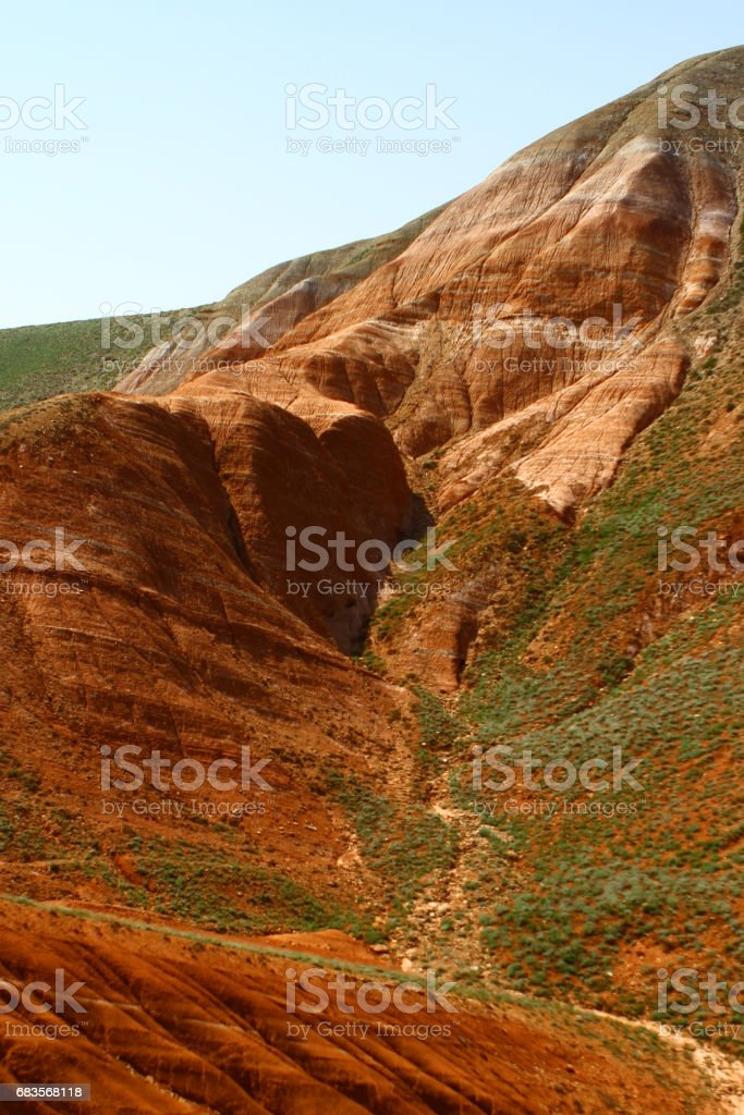 Layered eroded mountains with the green grassy slope stock photo