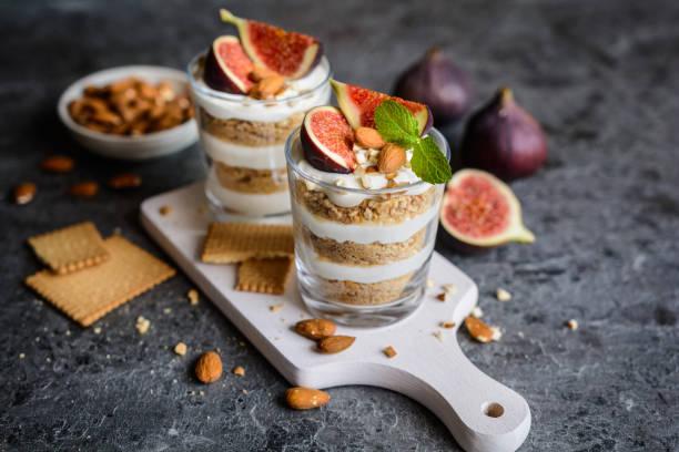 mascarpone-dessert mit zerkleinerten vanille kekse, feigen und mandeln geschichtet - dessert mit quark stock-fotos und bilder