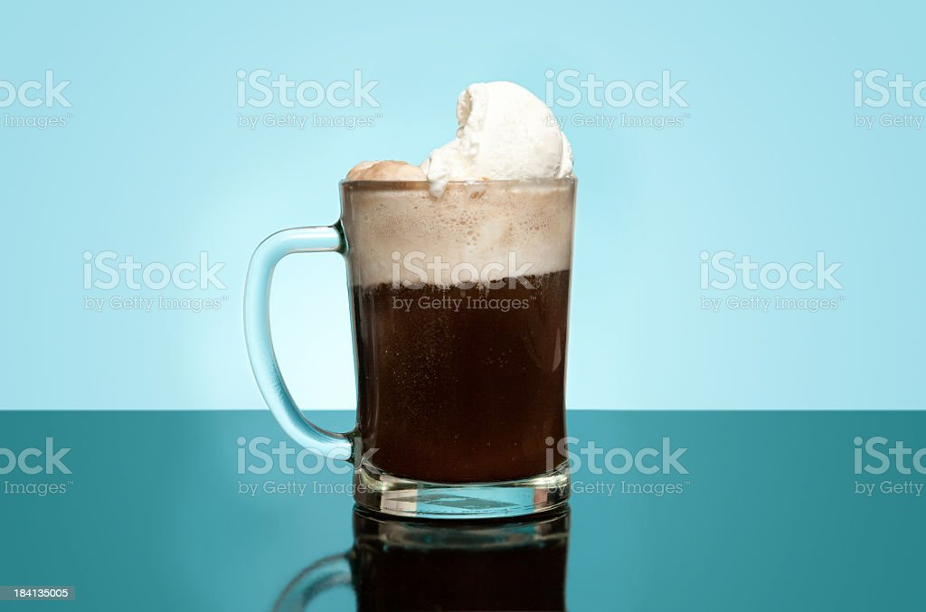 Layered Root beer float in a glass mug with dim blue back stock photo