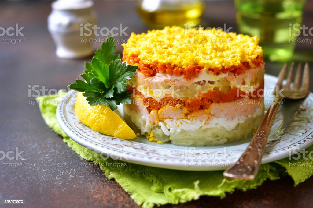 Layered salad with vegetables and salmon 'Mimosa' stock photo