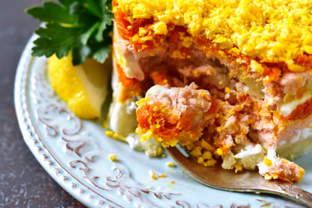 "layered salad with vegetables and salmon ""mimosa"" - mimosa cake foto e immagini stock"