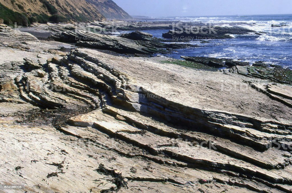Layered sedimentary rocks eroded by ocean waves in Montana de Oro State Park California stock photo