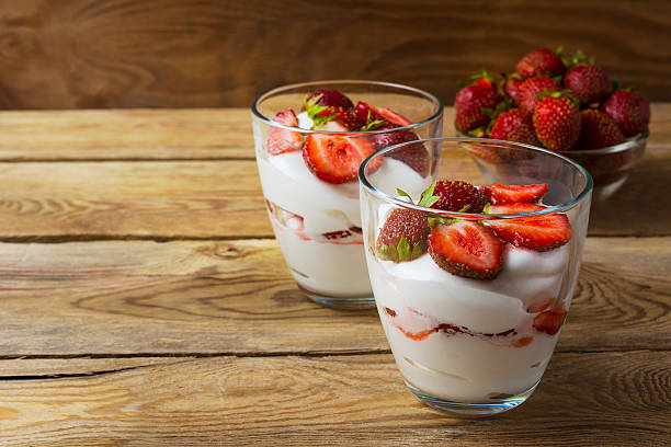 layered strawberry dessert on wooden background - mascarpone creme stock-fotos und bilder