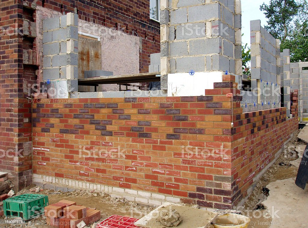Layering bricks to build a house, side view royalty-free stock photo