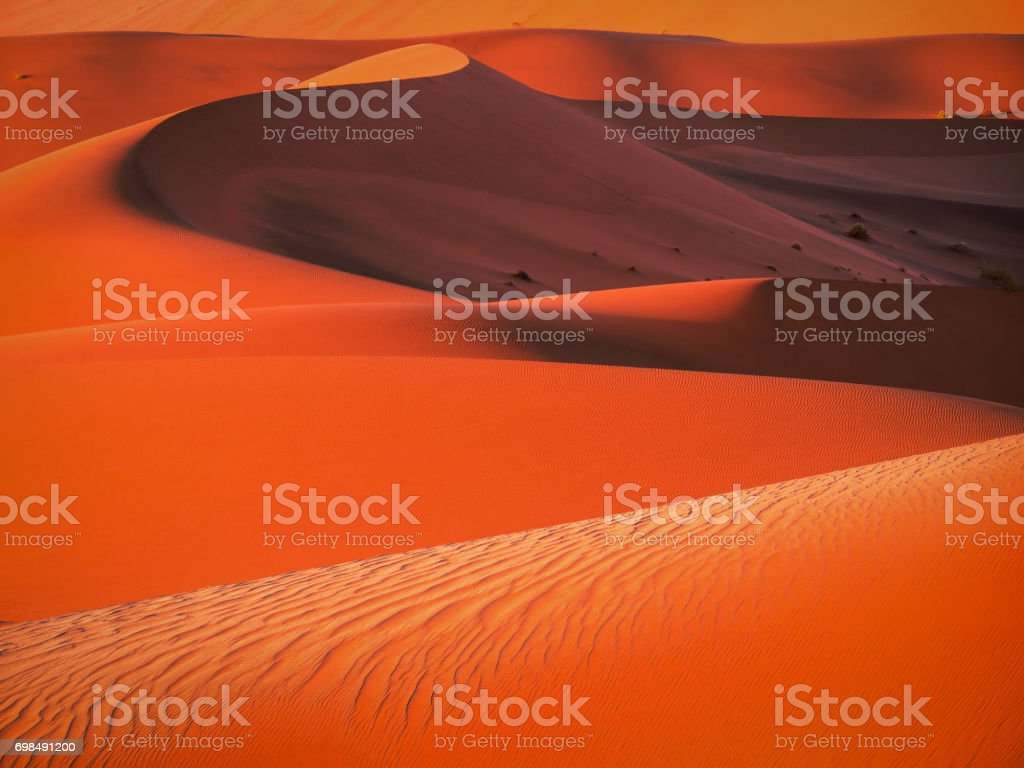 Layers and curves of red sand dunes at dawn with defined sand ripple patterns and shadows in Namibia. stock photo