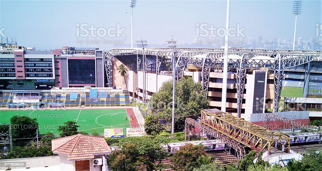 Layers of city Mumbai, India - 29 September, 2015: City skyline followed by sports stadiums which is followed by a train passing beneath a skywalk and lastly a small brick hut and trees. City Stock Photo