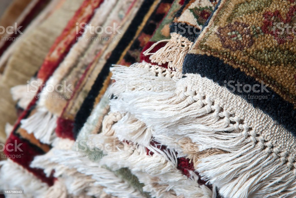 Layers of colorful Persian rugs piled on top of each other stock photo