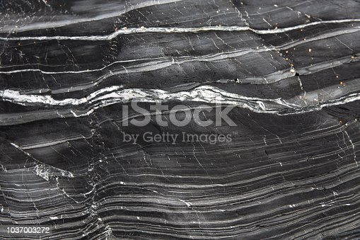 A geology background of layers of grey slate and marble compacted together in a cross section of a cliff side with copy space