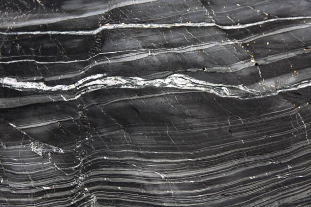 Layers of textured slate and marble A geology background of layers of grey slate and marble compacted together in a cross section of a cliff side with copy space marble rock stock pictures, royalty-free photos & images