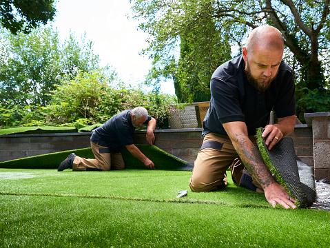 two workers fitting artificial grass in home garden