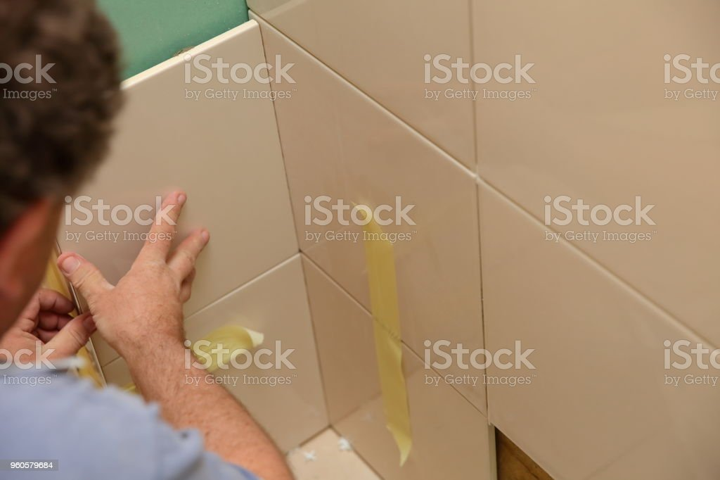 Laying ceramic tiles in the bathroom requires a lot of experience and patience to plan well and then evenly and accurately arrange the glaze on the wall. stock photo