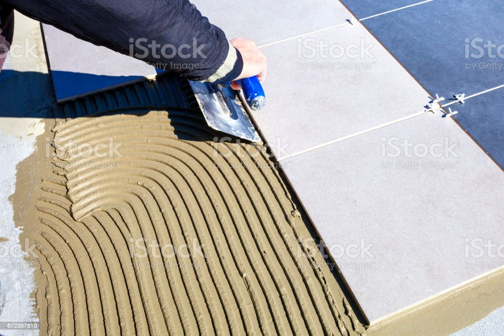 Laying ceramic tiles. Laying tiles on the floor. The glaziers lay ceramic tiles. stock photo