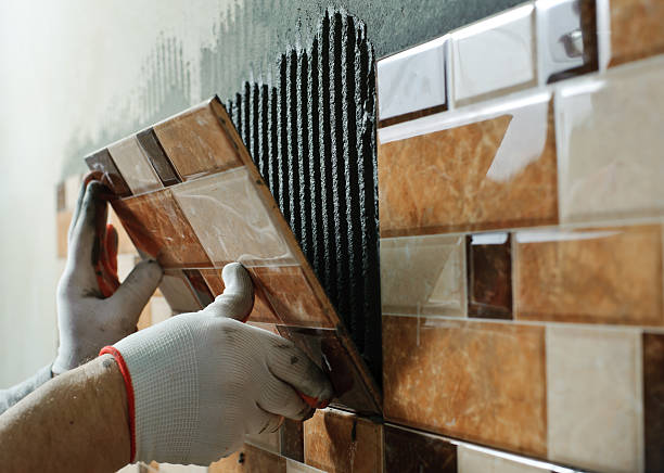 Laying Ceramic Tiles. Laying Ceramic Tiles. Tiler placing ceramic wall tile in position over adhesive ceramics stock pictures, royalty-free photos & images