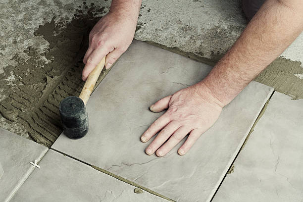 Laying ceramic tiles. Renovation - Man construction worker laying floor tile affix stock pictures, royalty-free photos & images