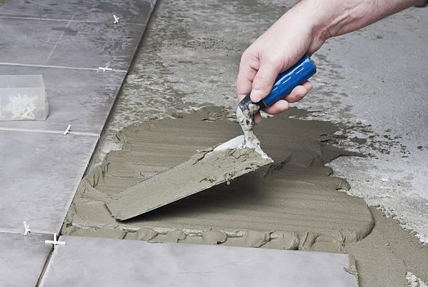 laying ceramic tiles. - keramik fliesen handwerk stock-fotos und bilder