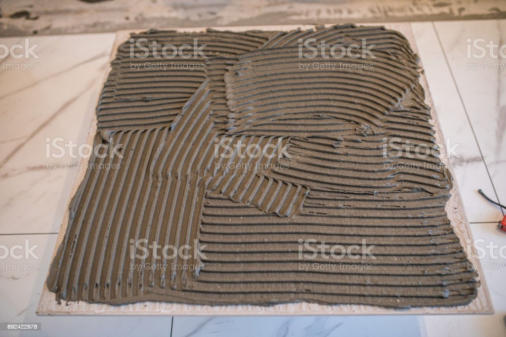 Laying Ceramic Tiles. Troweling adhesive for ceramic tile flooring stock photo