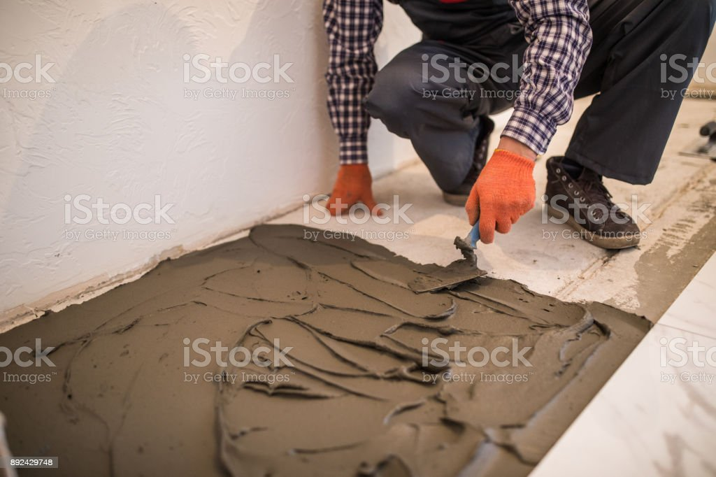 Laying Ceramic Tiles. Troweling mortar onto a concrete floor in preparation for laying white floor tile. stock photo