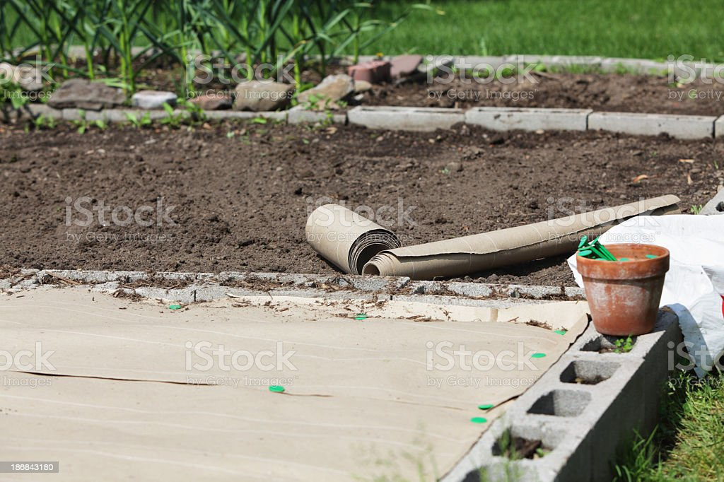 Laying Down New Garden Biodegradable Recycled Paper Weed Prevention Cover royalty-free stock photo