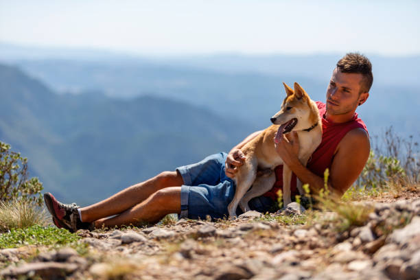 A laying down young man and his dog at the top of Montserrat mountain, Barcelona stock photo