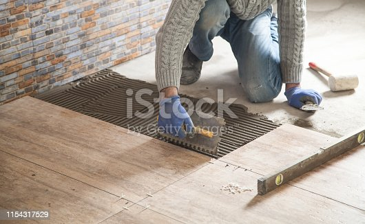 istock Laying floor ceramic tile. Renovating the floor 1154317529