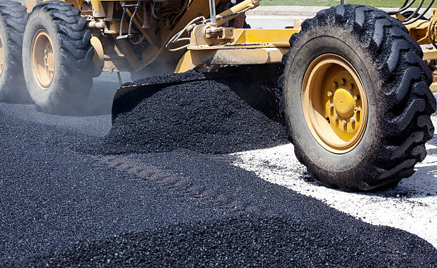 Laying fresh asphalt on construction site stock photo