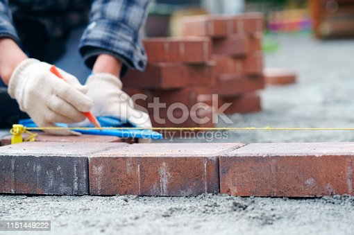 Laying gray concrete paving slabs in house and tools