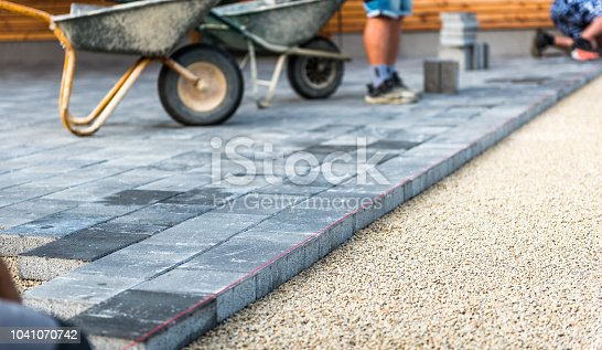 Laying gray concrete paving slabs in house courtyard driveway patio. Professional workers bricklayers are installing new tiles or slabs for driveway, sidewalk or patio on leveled  foundation base made of sand at public or private residence.
