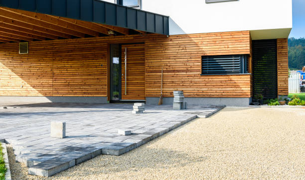 Laying gray concrete paving slabs in house courtyard driveway patio. stock photo