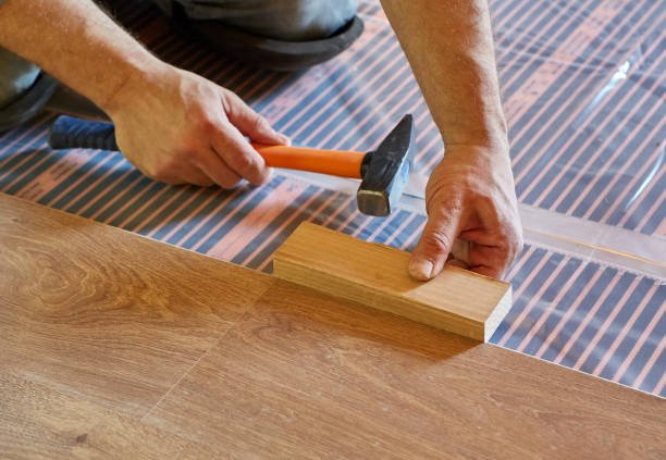 Laying laminate covering on heat-insulated floor stock photo