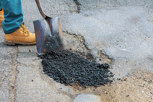 Laying new asphalt, covering the pit, hole in asphalt with very bad quality road