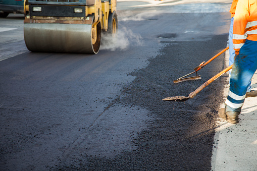 Two manual workers helping to level the asphalt surface for a steamroller to press.