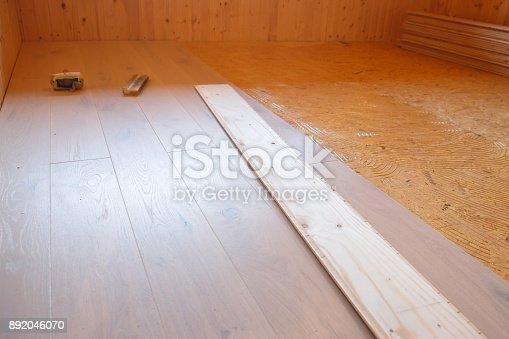 istock Laying of new parquet flooring in progress 892046070