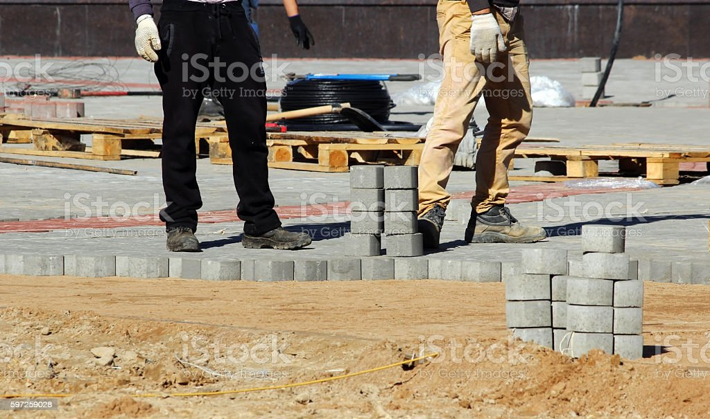 laying paving slabs on city square, repairing sidewalk. stock photo