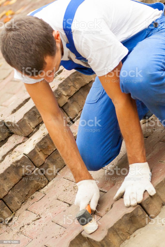 laying paving slabs on city square, repairing sidewalk stock photo