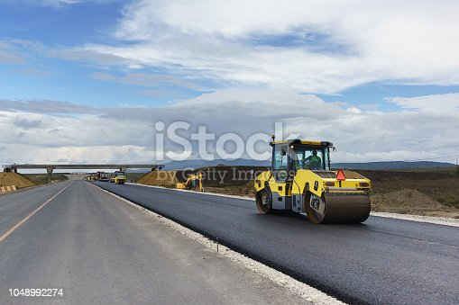 istock Laying the next layer of asphalt in the construction of a new road Tavrida in the Crimea. The crossing of roads is equipped with safe bridge crossings 1048992274