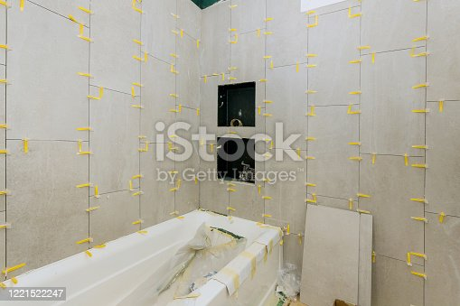 1138442636 istock photo Laying tiles in the bathroom construction floor and wall tile unfinished apartments 1221522247