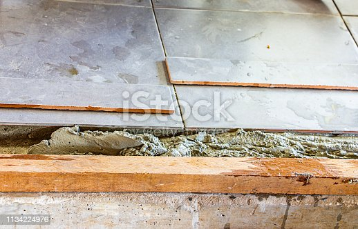 1138442636 istock photo laying tiles on floor at home, construction worker renovation laying tile under the concrete floor. 1134224976
