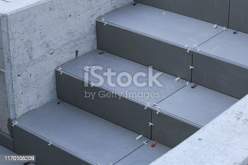istock Laying tiles on stepps outside 1170105209