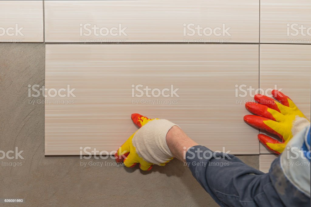 laying tiles on the wall stock photo