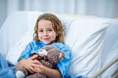 A Caucasian girl is indoors in a hospital room. She is smiling at the camera while holding a teddy bear.