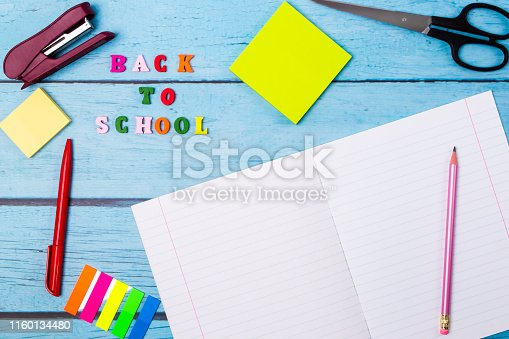 istock Layout of school supplies on a blue wooden background. The view from the top. Back to school. Flat lay. 1160134480