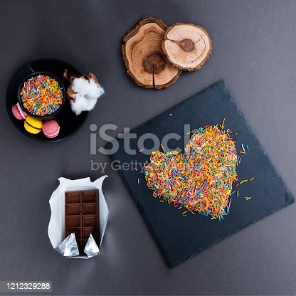 A layout of sweets, chocolate, hearts on a plate on a gray background. Minimal concept. Men's gift.