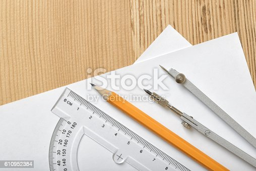 611108702 istock photo Layout with protractor, pencil and compass on white paper 610952384