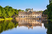 The Łazienki Palace, also known as the Baths Palace, reflecting in a lake in Warsaw's Royal Baths Park, the largest park in Warsaw, Poland.