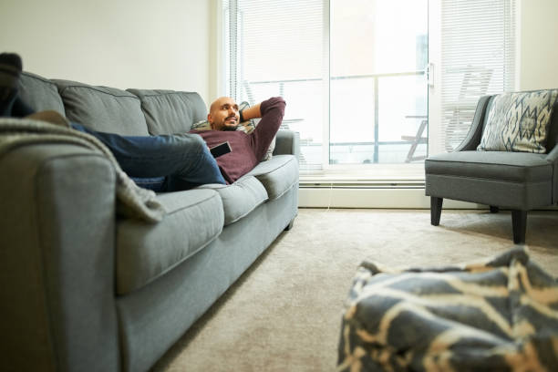 lazy day spent in front of tv - divano procrastinazione foto e immagini stock