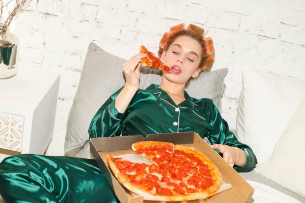 lui meisje in pyjama het eten van pizza in de slaapkamer - lazy stockfoto's en -beelden