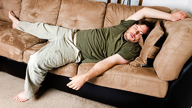 lazy guy flung all over the couch - laziness stock photos and pictures