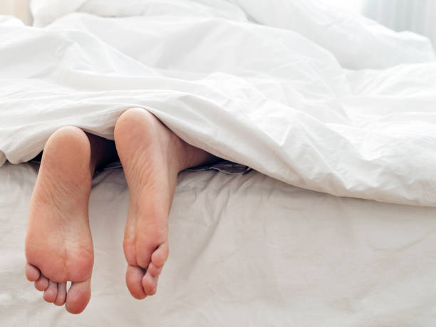 Lazy man and his feet ,  lying  on comfortable bed man feet taking  socks off supine position face down stock pictures, royalty-free photos & images