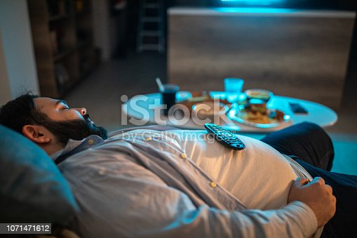 Overweight  man napping on couch at home in front of TV at night